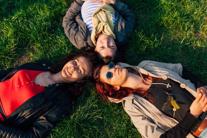 Muchachas que mienten en hierba foto de archivo
