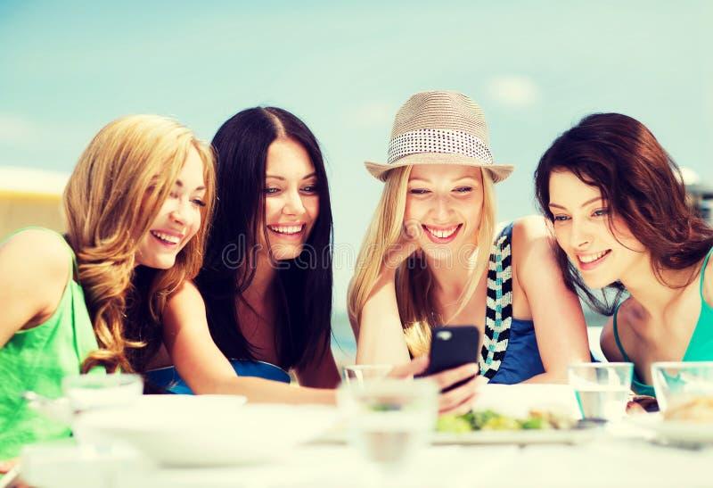Muchachas que miran smartphone en café en la playa fotos de archivo libres de regalías