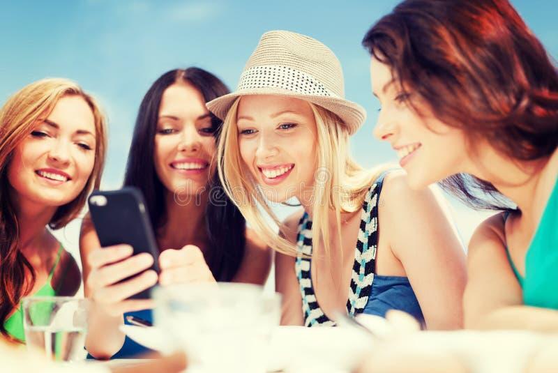 Muchachas que miran smartphone en café en la playa imágenes de archivo libres de regalías