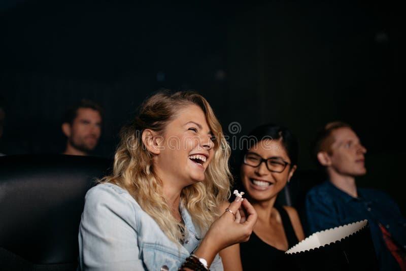 Muchachas que ríen y que miran película de la comedia fotos de archivo libres de regalías