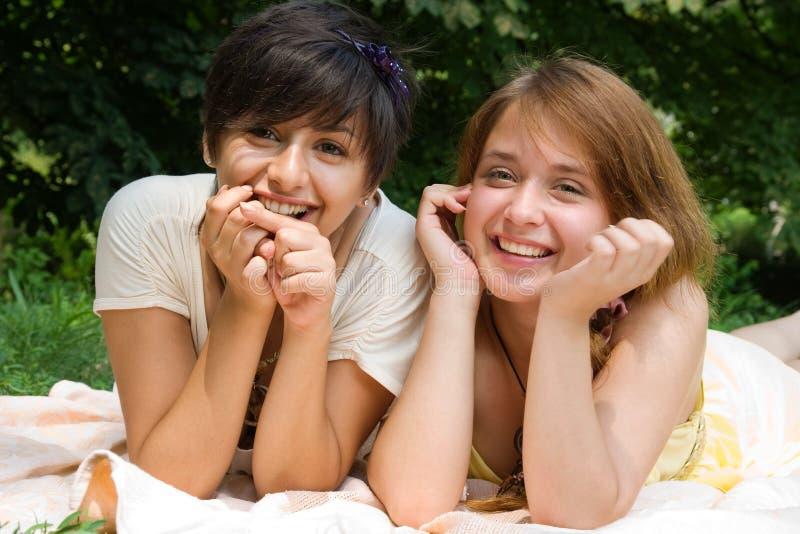 Muchachas que señalan con el dedo en algo que sonríe fotografía de archivo