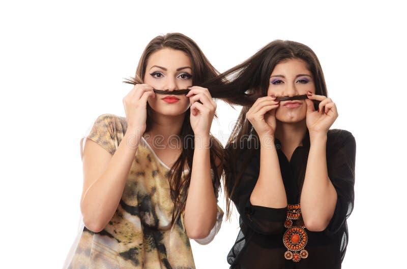 Muchachas que se divierten y que hacen bigotes fuera de cada otras el pelo fotografía de archivo