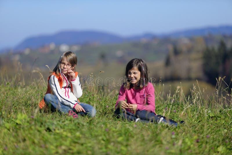 Muchachas que se sientan en hierba imagen de archivo libre de regalías