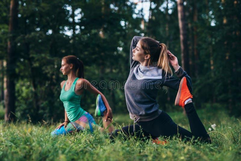 Muchachas que se sientan en una actitud de la paloma del rey de la pierna durante la sesión de formación en campo de la yoga foto de archivo