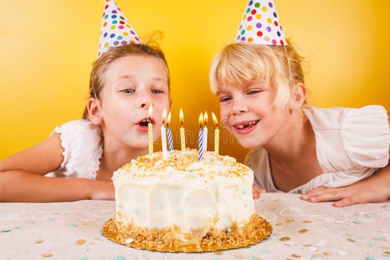 Muchachas que soplan hacia fuera velas en la torta de cumpleaños Famoso de la fiesta de cumpleaños fotos de archivo