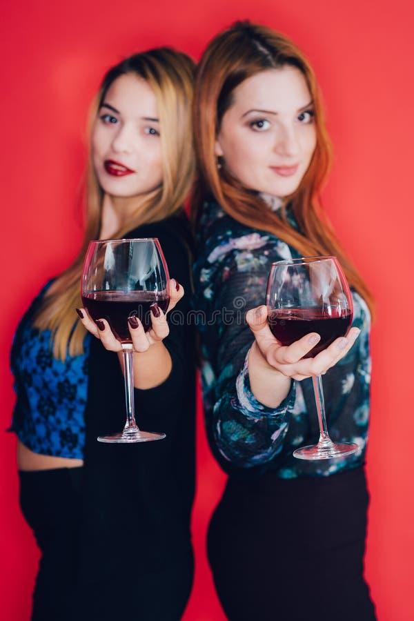 Muchachas que sostienen los vidrios de vino rojo imágenes de archivo libres de regalías