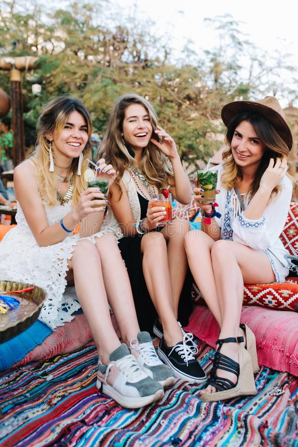 Muchachas sonrientes jovenes atractivas en vestidos de moda que pasan el tiempo junto en comida campestre del verano en el parque imagenes de archivo