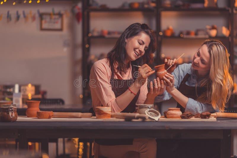Muchachas sonrientes jovenes en el trabajo dentro foto de archivo libre de regalías
