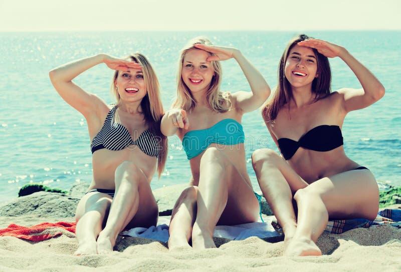 Muchachas sonrientes que se sientan en la playa imagenes de archivo