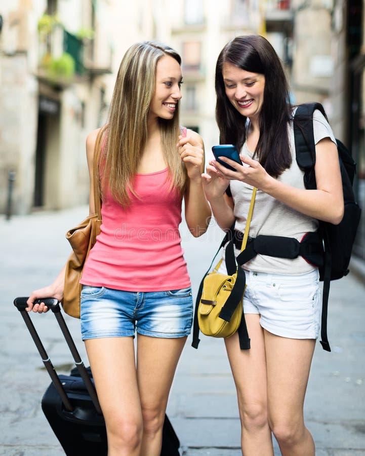 Muchachas sonrientes que usan el sistema de navegación del smartphone fotografía de archivo