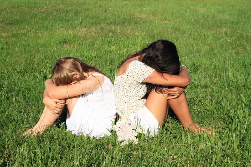 Muchachas tristes que se sientan en hierba imagen de archivo libre de regalías