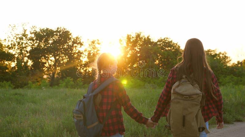 Muchachas turísticas en la carretera nacional La muchacha del caminante, las muchachas adolescentes viaja y lleva a cabo las mano foto de archivo