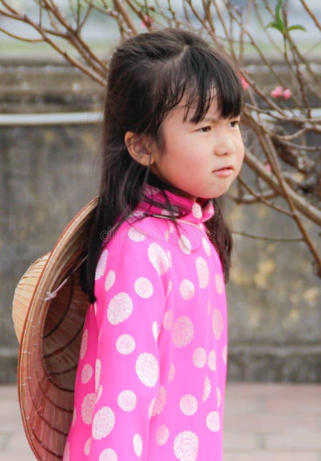 Muchachas vietnamitas de Ittle en traje nacional con el sombrero en Año Nuevo chino foto de archivo