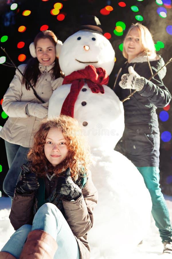 Muchachas y muñeco de nieve foto de archivo