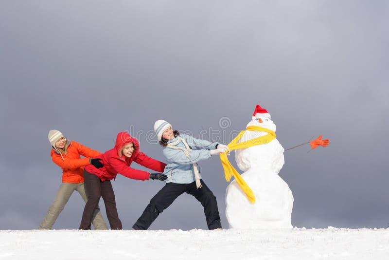 Muchachas y muñeco de nieve imagenes de archivo