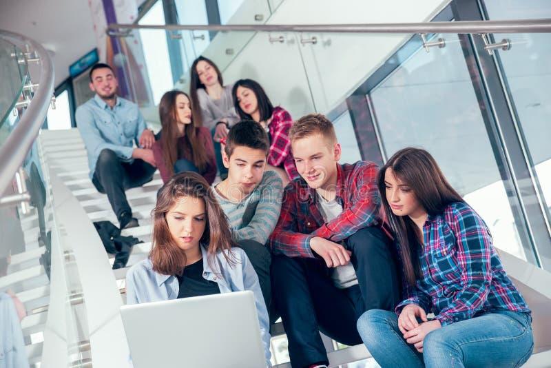 Muchachas y muchachos adolescentes felices en las escaleras escuela o universidad foto de archivo
