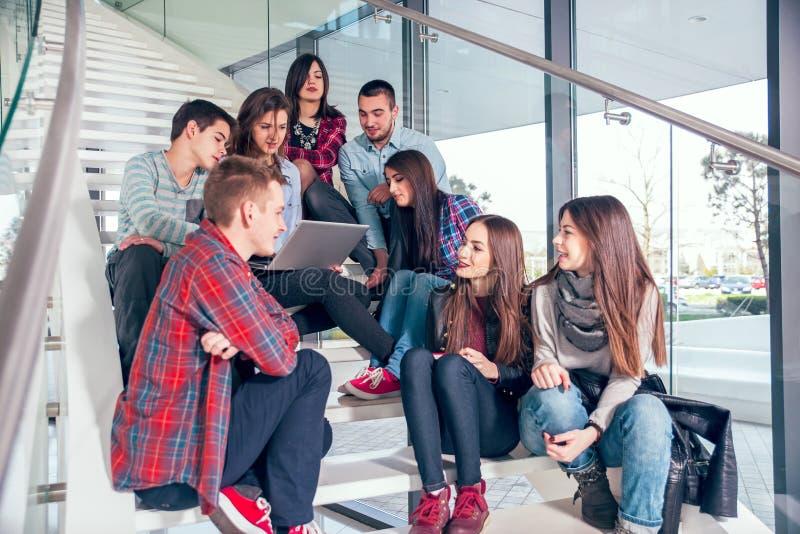 Muchachas y muchachos adolescentes felices en las escaleras escuela o universidad fotos de archivo libres de regalías