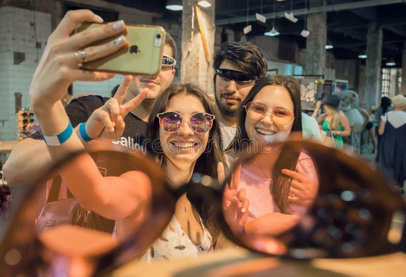 Muchachas y muchachos que se divierten y que hacen el selfie dentro de la tienda de las gafas de sol fotos de archivo