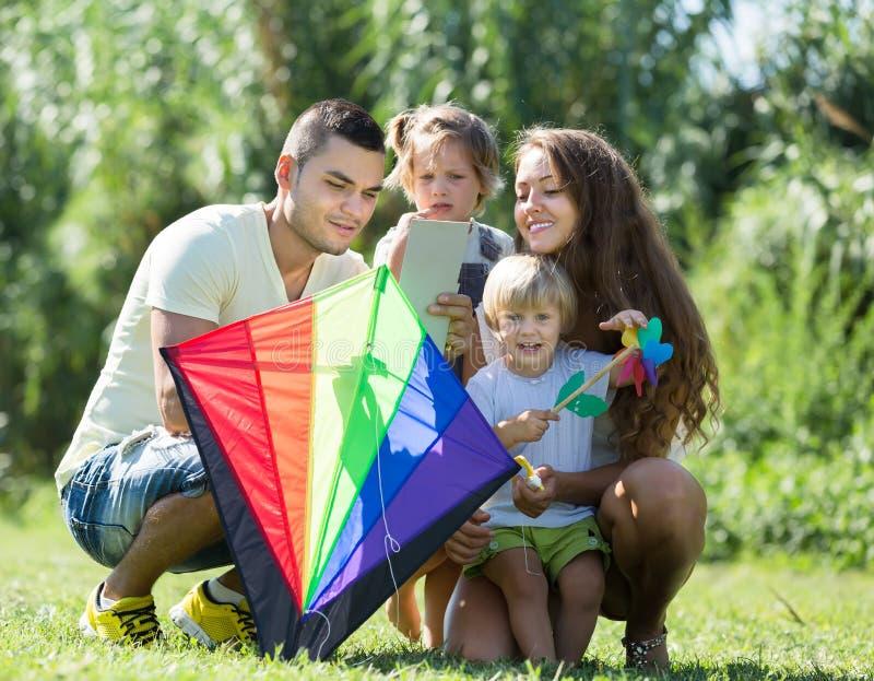 Muchachas y padres que juegan con la cometa fotos de archivo