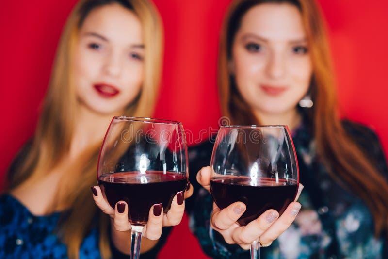 Muchachas y vidrios de vino rojo foto de archivo