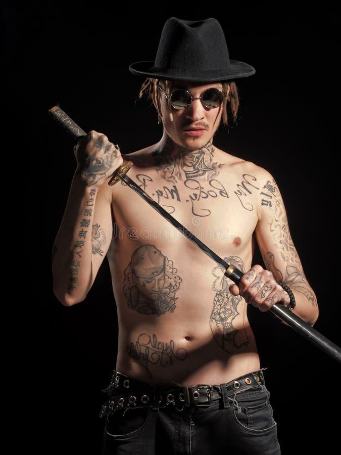 Muchacho accionado Muchachos de la cara de los problemas Hombre con el torso tatuado desnudo en el sombrero que sostiene la espad imagen de archivo