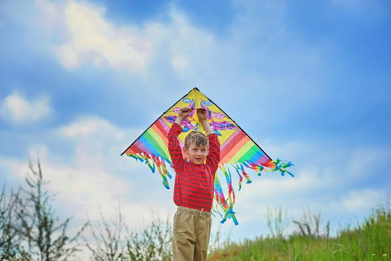 Muchacho activo que juega al aire libre con una cometa fotografía de archivo