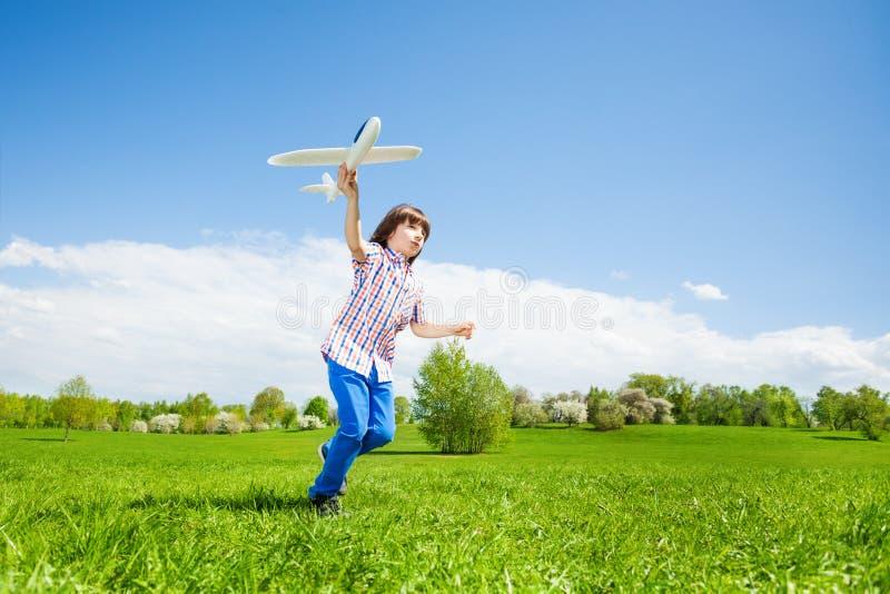 Muchacho activo que sostiene el juguete del aeroplano durante el funcionamiento foto de archivo libre de regalías