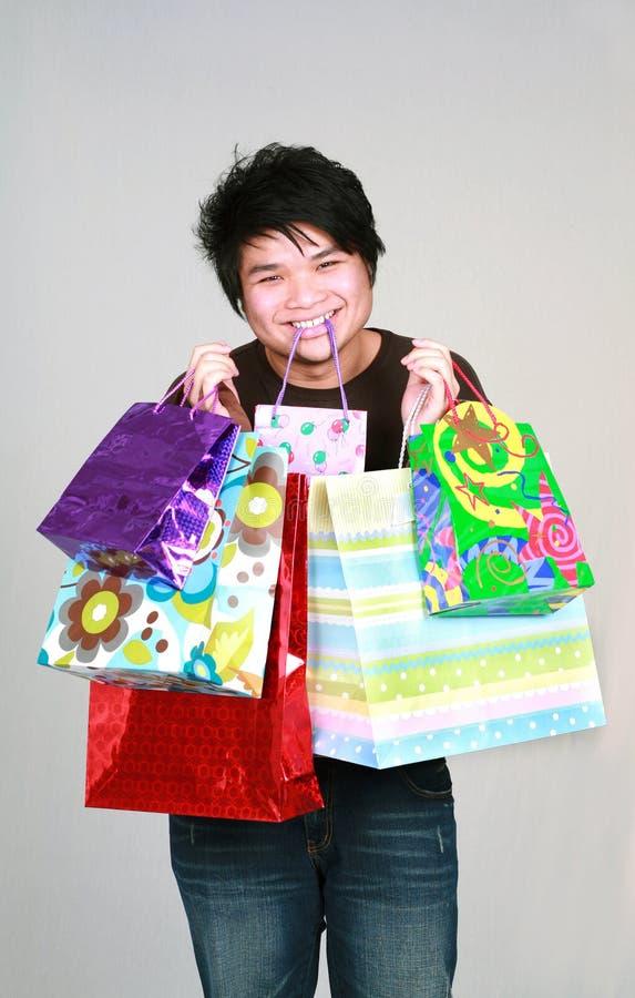 Muchacho adolescente asiático con los bolsos de los regalos imagenes de archivo