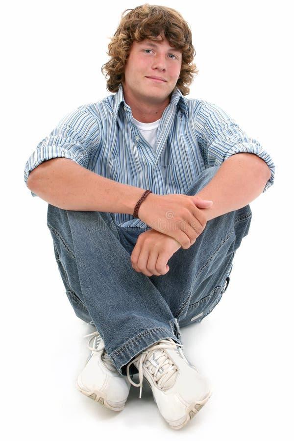 Muchacho adolescente atractivo de dieciséis años que se sienta en suelo
