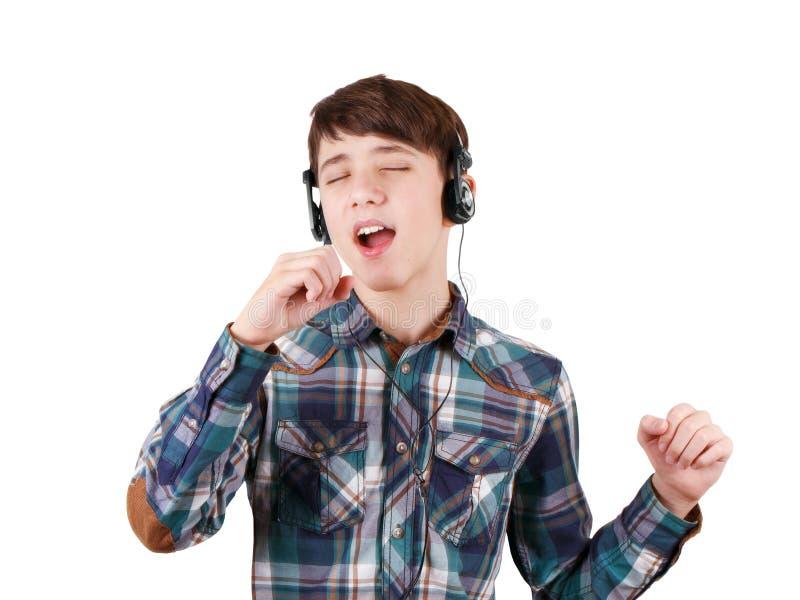 Muchacho adolescente cantante en auriculares que escucha la música y que muestra la muestra de la mano aislada en blanco imagen de archivo