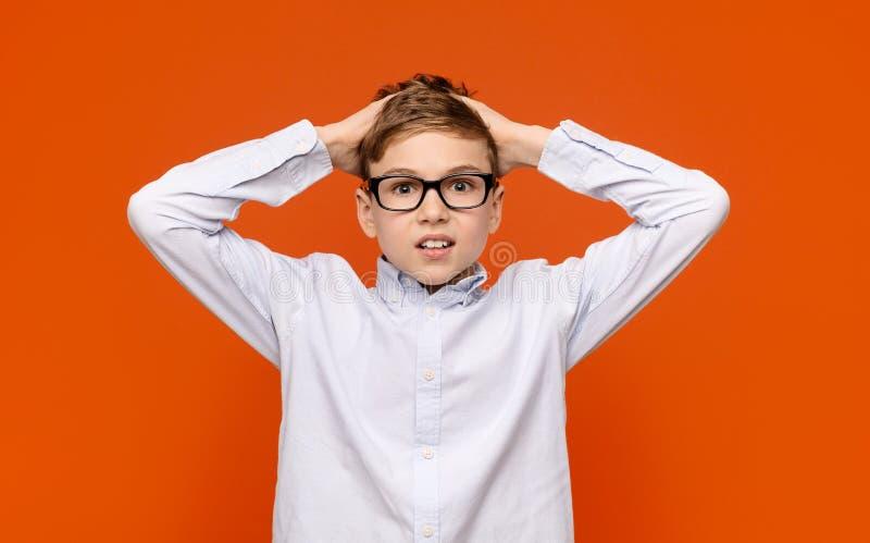 Muchacho adolescente chocado en los vidrios que tocan su cabeza en el asombro fotografía de archivo libre de regalías