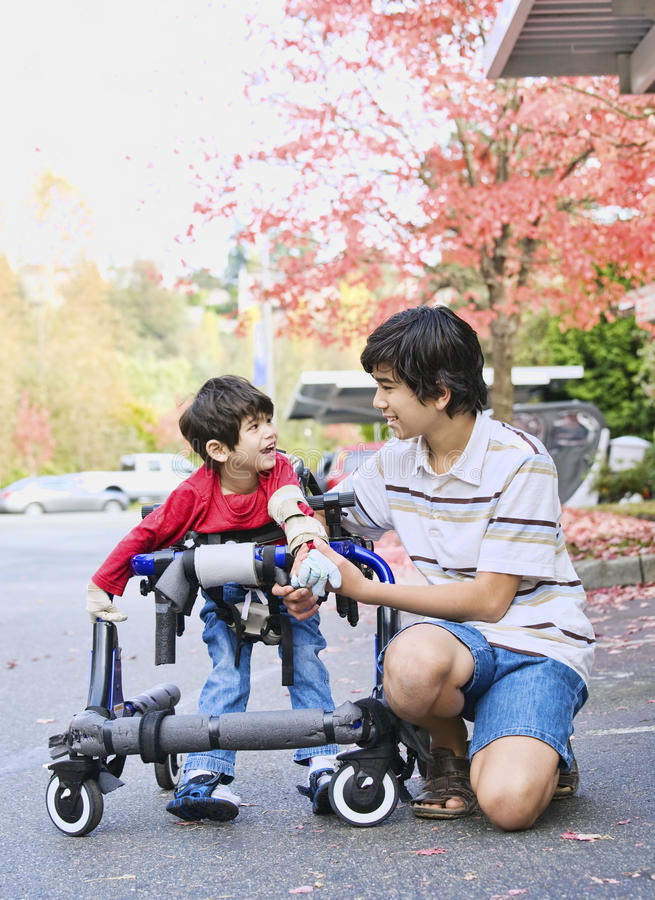 Muchacho adolescente con el pequeño hermano lisiado en caminante imagen de archivo