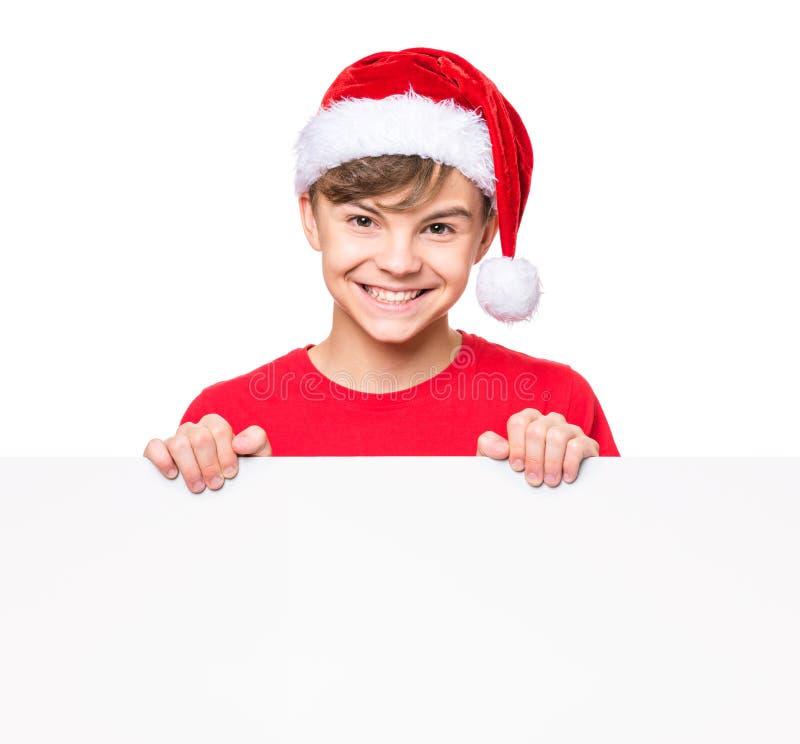 Muchacho adolescente con el sombrero de la Navidad foto de archivo