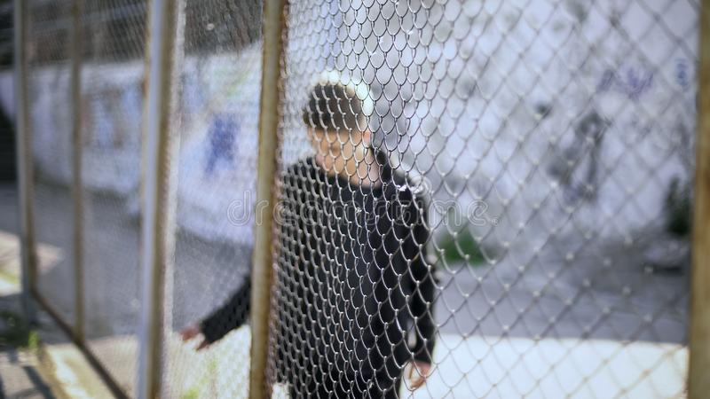 Muchacho adolescente detrás del confinamiento de la cerca, restricciones del colegio de internos, rotas futuro imagen de archivo libre de regalías
