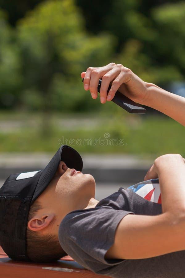 Muchacho adolescente feliz en la calle y usar el tel?fono elegante foto de archivo