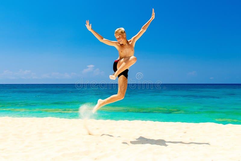 Muchacho adolescente feliz que se divierte en la playa tropical Vacaciones de verano foto de archivo