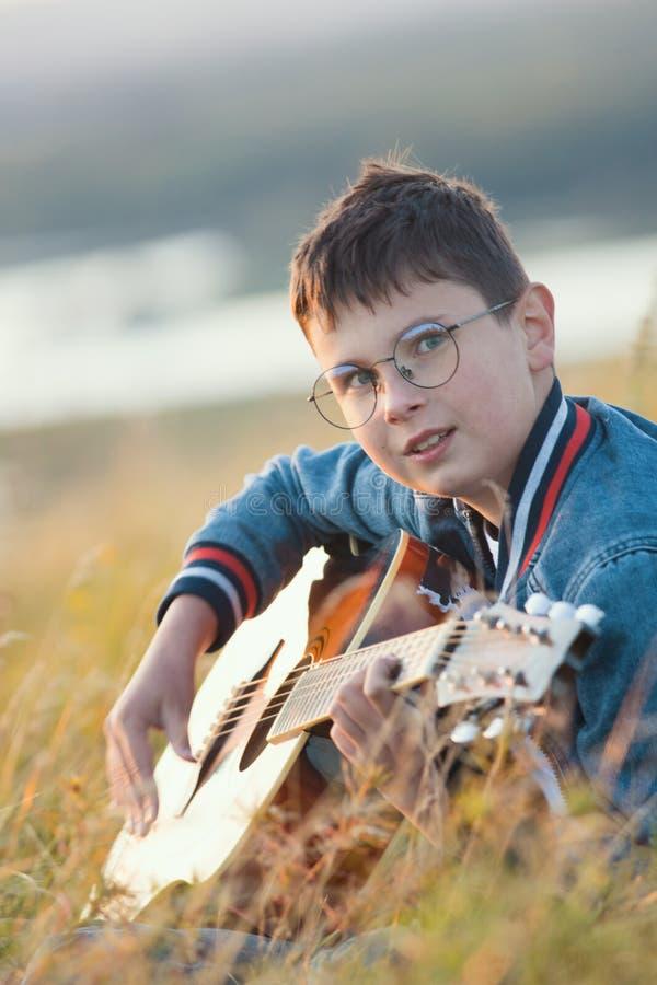 Muchacho adolescente joven que juega en la guitarra acústica en el campo del verano en puesta del sol y que mira a la cámara fotos de archivo libres de regalías