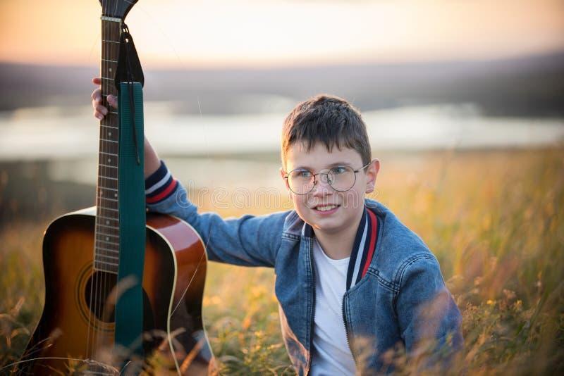 Muchacho adolescente joven que sostiene la guitarra acústica en el campo del verano en puesta del sol y la sonrisa imagen de archivo