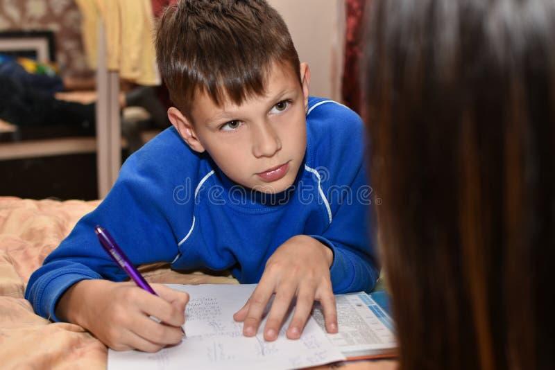Muchacho adolescente por la tarde que hace la preparación de la escuela con la madre en el cuarto en la cama fotos de archivo