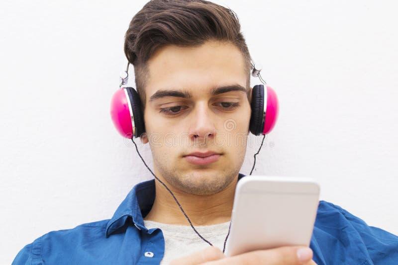 Muchacho adolescente serio con los auriculares y el teléfono móvil imágenes de archivo libres de regalías