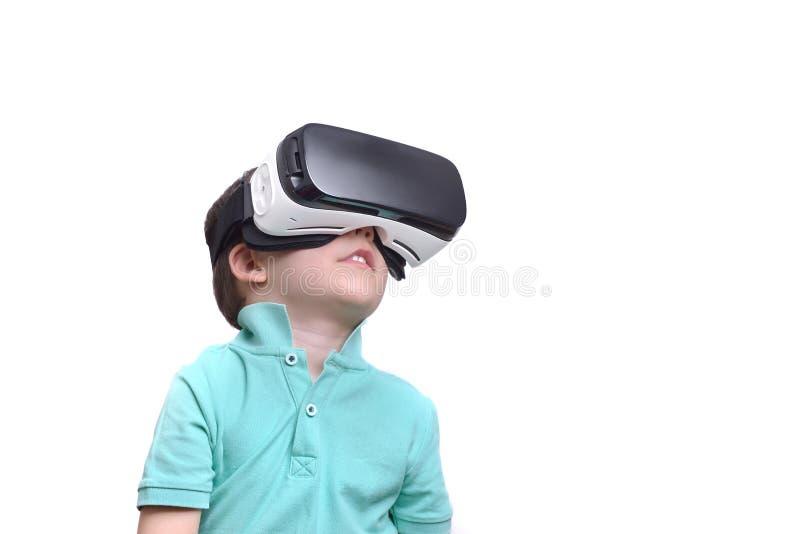 Muchacho adolescente sorprendente que lleva las gafas de la realidad virtual que miran películas o que juegan a los videojuegos,  fotos de archivo libres de regalías