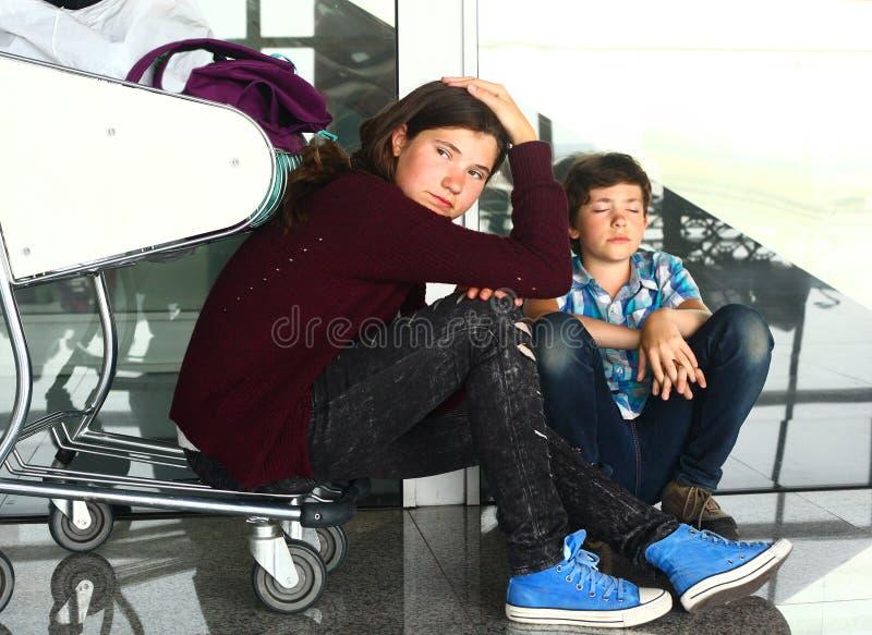 Muchacho adolescente y muchacha que esperan en el aeropuerto imagenes de archivo