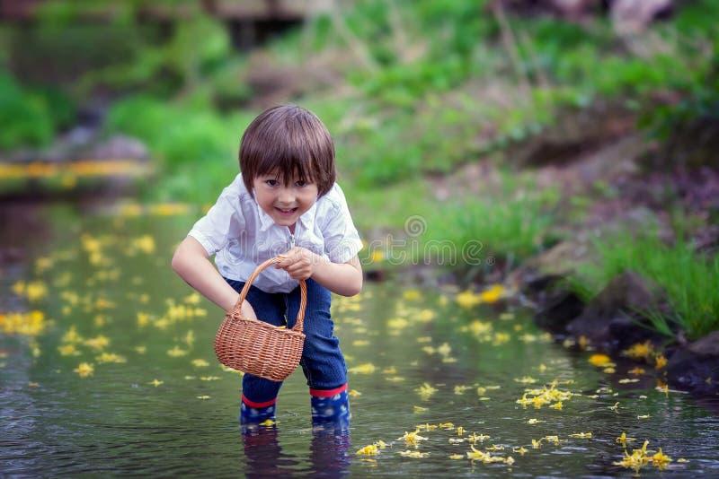 Muchacho adorable con poca cesta, llena de flores en un poco pon fotografía de archivo