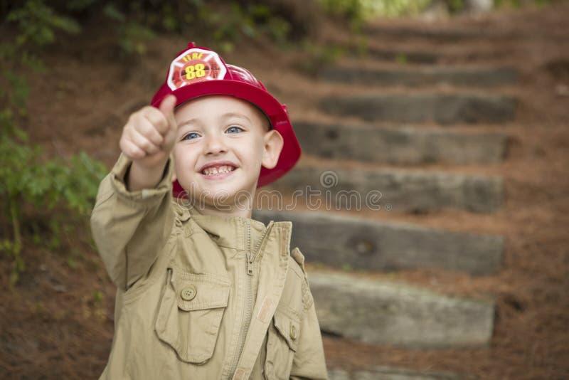 Muchacho adorable del niño con jugar del sombrero del bombero foto de archivo libre de regalías