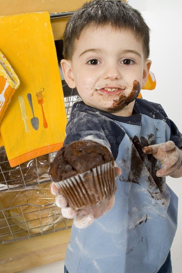 Muchacho adorable del niño que comparte el mollete del chocolate foto de archivo libre de regalías