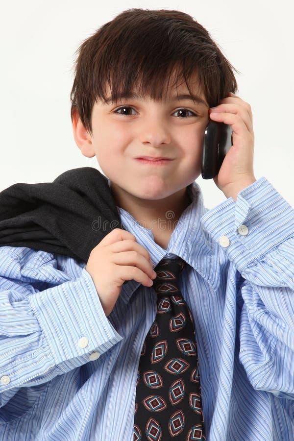 Muchacho adorable en juego holgado con el teléfono celular fotos de archivo