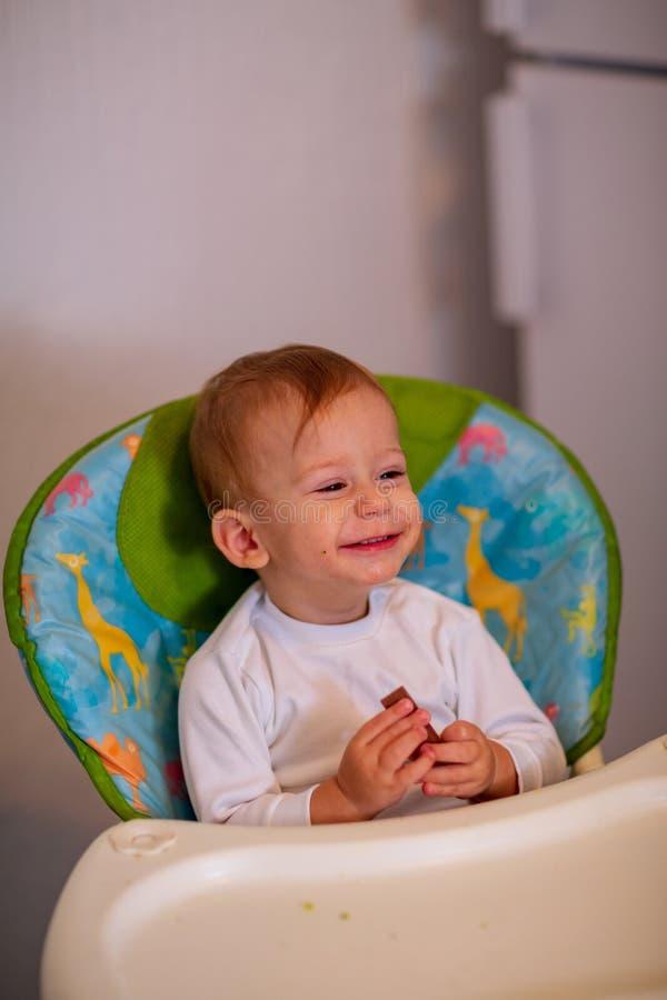 """Muchacho adorable feliz del †de alimentación del bebé el """"que come chocolate fotos de archivo"""