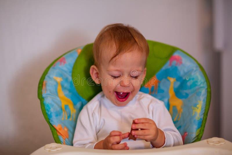 Muchacho adorable feliz que come el chocolate delicioso imagen de archivo