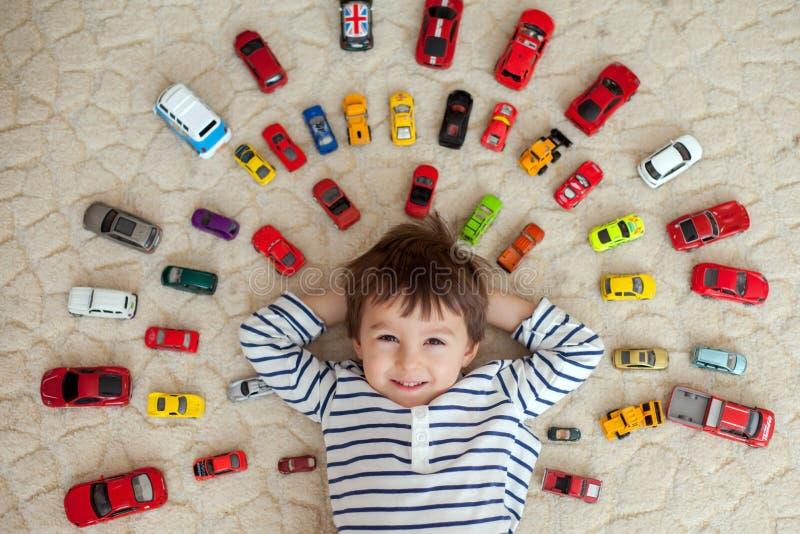 Muchacho adorable, mintiendo en la tierra, coches del juguete alrededor de él fotos de archivo libres de regalías