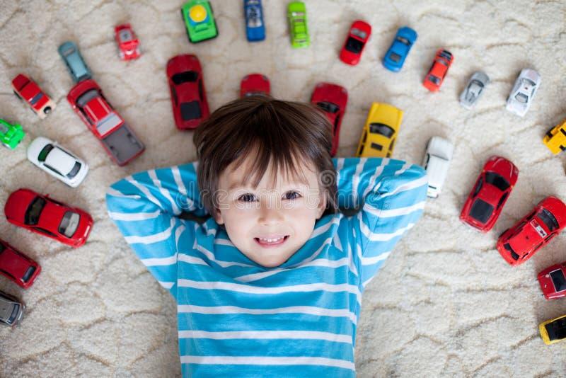 Muchacho adorable, mintiendo en la tierra, coches del juguete alrededor de él, mirando fotos de archivo libres de regalías